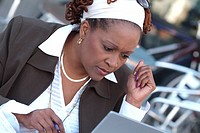 Frowning African businesswoman looking at laptop