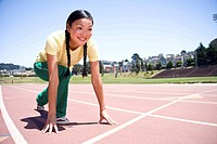 Asian woman running on race track