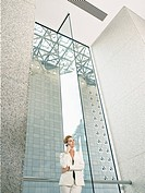 Businesswoman using mobile phone in office building low angle view