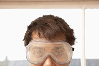 Man wearing protective eye goggles indoors close up high section
