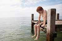 Pre-teen boy sitting on end of pier with feet in water portrait (thumbnail)