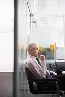 Mature businessman sitting in conference room side view (thumbnail)