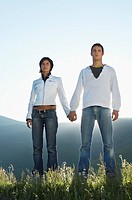 Young couple standing in mountain field looking at view front view low angle view