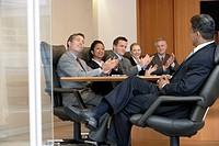 Business people applauding man in office meeting