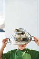 Young boy with colander on head head and shoulders