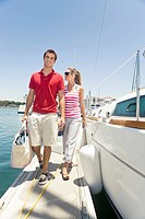 Couple walking along boats in harbor