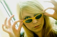 Young blond woman, wearing sunglasses, standing by her living room window