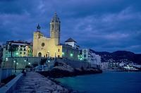 Illuminated church of Sant Bartomeu i Santa Tecla at night, Sitges, Costa del Garraf, Spain