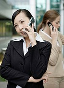 Two business women using cell phone and looking away