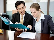 Business man discussing with business woman and looking at the files together