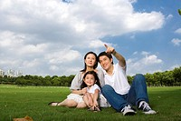 Family with daughter sitting on lawn, father pointing