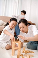 Mother and daughter playing blocks, father reading newspaper