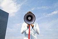 portrait of young businesswoman hidden behind megaphone