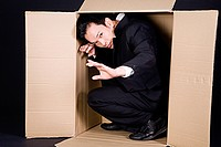 portrait of man hiding in cardboard box