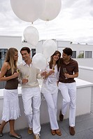Group, stands, smiling, celebrates, champagne_glasses, celebration, balloon, holding, full_length outside,