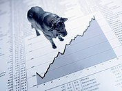 Bull figurine on ascending line graph and list of share prices