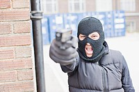 Man in skin mask holding gun