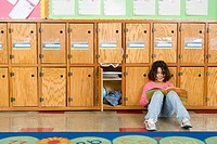 Girl leaning against cubby holes in classroom