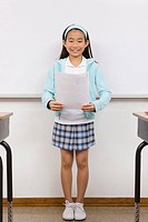 Girl reading report aloud in classroom