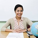 Teacher sitting at desk in classroom