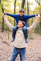 Father carrying his son in a wood