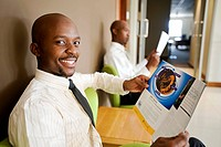 Businessman looks into camera while reading in an office. Pretoria, South Africa