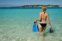 A tourist walks into the sea with snorkelling equipment, Mauritius