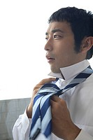 Businessman putting on a tie (thumbnail)