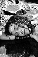 Close up of nude Caucasian mid adult woman lying in water at coast with head resting on arm