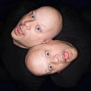 Aeriel view of Caucasian bald identical twin men sitting back to back making facial expressions