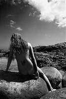 Back view of young nude Asian woman sitting on rocks 