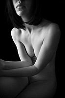 Nude young adult Caucasian female body sitting