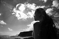 Young nude Asian woman looking out towards ocean with hair blowing in wind