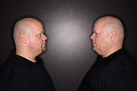 Bald identical twin men standing face to face