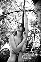 Young adult Caucasian nude woman holding onto hanging vine 