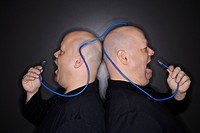 Bald identical twin men standing back to back yelling into ethernet cable