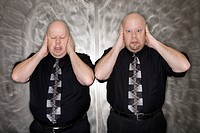 Caucasian bald mid adult identical twin men standing with hands covering ears making facial expression
