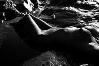 Close up of Filipino young nude woman lying on back in water on rocky beach