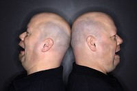 Caucasian bald mid adult identical twin men standing back to back with sad expressions