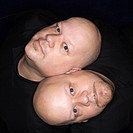 Aerial view of bald identical twin men sitting back to back and looking up at viewer