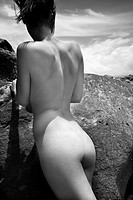 Rear view of young nude Caucasian woman leaning against rock