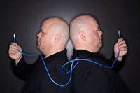 Caucasian bald mid adult identical twin men standing back to back holding ethernet cable