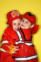 Caucasian twin boys dressed as firemen hugging against yellow background