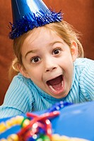 Caucasian girl wearing party hat holding gift and looking at viewer with excited expression