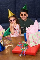 Hispanic brother and sister wearing sunglasses and party hats sitting with presents having a birthday party