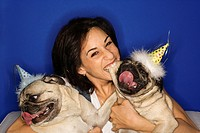 Caucasian prime adult female holding two Pug dogs