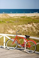 Red beach cruiser bicycle leaning against walkway rail on beach on Bald Head Island, North Carolina (thumbnail)