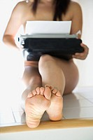 Young nude Asian woman holding typewriter on lap sitting on kitchen table