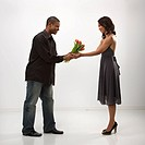 African American mid adult man giving woman bouquet of flowers (thumbnail)