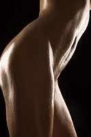 Side view of thighs and stomach of nude Hispanic mid adult woman glistening with body oil